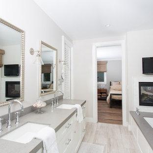 Idee per una stanza da bagno padronale stile marino con lavabo sottopiano, ante con riquadro incassato, ante bianche, vasca sottopiano, pareti grigie, pavimento in vinile e top grigio