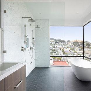 Foto de cuarto de baño contemporáneo con armarios con paneles lisos, puertas de armario de madera en tonos medios, bañera exenta, lavabo bajoencimera, suelo negro y encimeras blancas