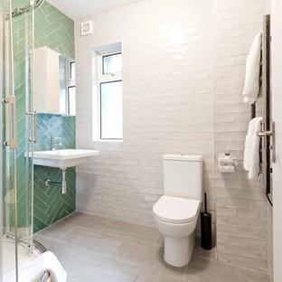 ダブリンの中くらいのコンテンポラリースタイルのおしゃれな子供用バスルーム (フラットパネル扉のキャビネット、一体型トイレ、緑のタイル、白いタイル、緑の壁、壁付け型シンク、白いキャビネット、コーナー設置型シャワー、磁器タイル、磁器タイルの床、珪岩の洗面台、グレーの床、引戸のシャワー) の写真