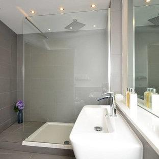 Imagen de cuarto de baño principal, minimalista, de tamaño medio, con ducha abierta, sanitario de pared, baldosas y/o azulejos blancos, baldosas y/o azulejos de porcelana, paredes blancas, suelo de baldosas de porcelana, lavabo suspendido y encimera de esteatita