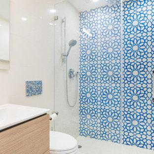 Idée de décoration pour une salle de bain design de taille moyenne avec un placard à porte plane, des portes de placard beiges, un carrelage bleu, un carrelage multicolore, un mur blanc, une cabine de douche à porte battante, des carreaux de céramique, un sol en bois brun, une grande vasque, un plan de toilette en surface solide, un sol marron et un plan de toilette blanc.