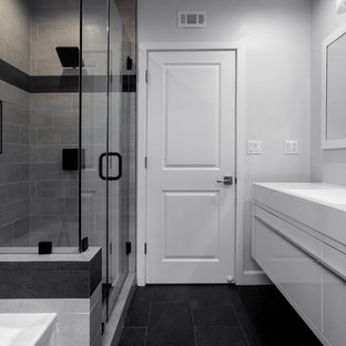 Inspiration for a medium sized modern family bathroom in Los Angeles with flat-panel cabinets, white cabinets, an alcove bath, a walk-in shower, a one-piece toilet, grey tiles, porcelain tiles, white walls, slate flooring, an integrated sink, solid surface worktops, black floors, a hinged door and white worktops.