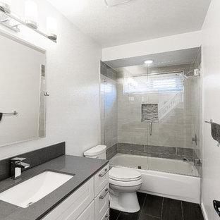 Idéer för ett mellanstort modernt grå badrum med dusch, med skåp i shakerstil, vita skåp, ett badkar i en alkov, en dusch/badkar-kombination, en toalettstol med hel cisternkåpa, vita väggar, vinylgolv, ett undermonterad handfat, granitbänkskiva, svart golv och dusch med gångjärnsdörr
