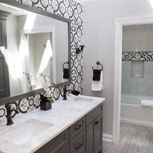 Exempel på ett mellanstort klassiskt flerfärgad flerfärgat badrum för barn, med luckor med infälld panel, grå skåp, ett badkar i en alkov, en dusch/badkar-kombination, en toalettstol med separat cisternkåpa, flerfärgad kakel, keramikplattor, grå väggar, klinkergolv i porslin, ett undermonterad handfat, bänkskiva i kvarts, flerfärgat golv och dusch med gångjärnsdörr