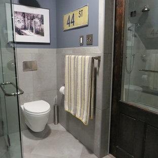 Foto de cuarto de baño con ducha, industrial, pequeño, con lavabo bajoencimera, armarios con paneles empotrados, puertas de armario de madera en tonos medios, ducha a ras de suelo, sanitario de pared, baldosas y/o azulejos de porcelana, paredes grises, suelo de baldosas de porcelana y baldosas y/o azulejos grises