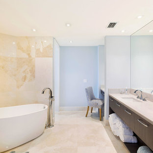 Mid-sized transitional master bathroom in Miami with flat-panel cabinets, brown cabinets, a freestanding tub, beige tile, blue walls, an undermount sink, beige floor, beige benchtops, a one-piece toilet, limestone, porcelain floors and marble benchtops.