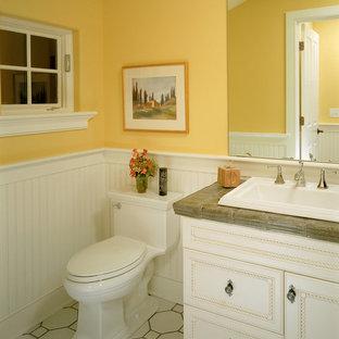 Foto på ett vintage badrum, med ett nedsänkt handfat, luckor med infälld panel, vita skåp, kaklad bänkskiva, en toalettstol med hel cisternkåpa, gula väggar och vitt golv