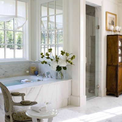 Alcove shower - traditional white tile marble floor alcove shower idea in Dallas with dark wood cabinets and an undermount tub