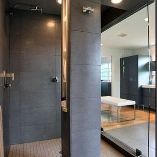 Large minimalist master light wood floor bathroom photo in New York with flat-panel cabinets, gray cabinets, beige walls, a wall-mount sink and solid surface countertops