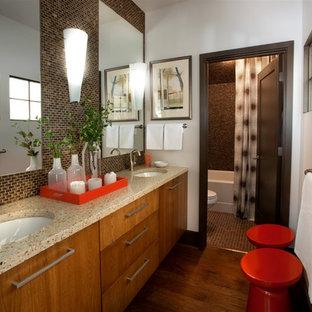 Foto de cuarto de baño principal, tradicional renovado, de tamaño medio, con encimera de granito, armarios con paneles lisos, puertas de armario de madera oscura, baldosas y/o azulejos beige, baldosas y/o azulejos marrones, baldosas y/o azulejos de vidrio, paredes blancas, suelo de madera en tonos medios, lavabo bajoencimera, sanitario de una pieza, suelo marrón, bañera empotrada, combinación de ducha y bañera y ducha con cortina