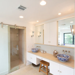 Trendy gray tile and mosaic tile bathroom photo in Austin with a vessel sink, flat-panel cabinets and white cabinets