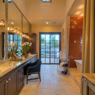 Foto de cuarto de baño principal, mediterráneo, grande, con baldosas y/o azulejos naranja, armarios con paneles empotrados, puertas de armario marrones, bañera exenta, baldosas y/o azulejos de cerámica, suelo de travertino, lavabo sobreencimera, encimera de ónix y suelo beige