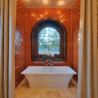 Idee per una grande stanza da bagno padronale mediterranea con vasca freestanding, ante con riquadro incassato, ante marroni, piastrelle arancioni, piastrelle in ceramica, pareti rosse, pavimento in travertino, lavabo a bacinella, top in onice e pavimento beige