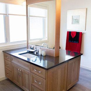 Ejemplo de cuarto de baño principal, contemporáneo, de tamaño medio, con lavabo bajoencimera, armarios estilo shaker, puertas de armario de madera clara, encimera de granito, baldosas y/o azulejos beige, paredes grises y suelo de baldosas de porcelana