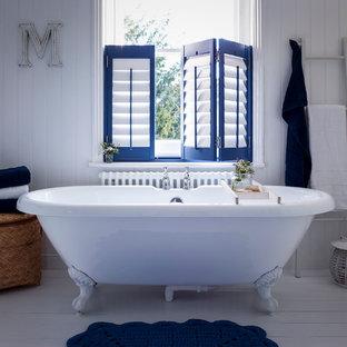 Imagen de cuarto de baño infantil, contemporáneo, de tamaño medio, con bañera exenta, paredes blancas y suelo de madera clara