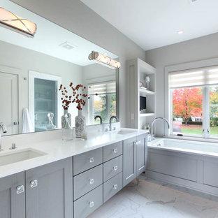 Foto di una stanza da bagno padronale chic di medie dimensioni con lavabo sottopiano, ante in stile shaker, ante grigie, top in quarzite, piastrelle in gres porcellanato, pareti grigie, pavimento in gres porcellanato e vasca sottopiano