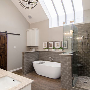 Transitional master bathroom in Dallas with shaker cabinets, white cabinets, a freestanding tub, gray tile, grey walls, medium hardwood floors, an undermount sink and a hinged shower door.