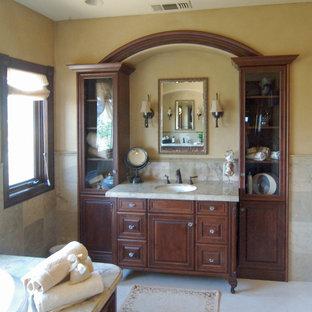 Свежая идея для дизайна: большая главная ванная комната в викторианском стиле с накладной раковиной, фасадами с выступающей филенкой, темными деревянными фасадами, столешницей из оникса, бежевой плиткой и каменной плиткой - отличное фото интерьера