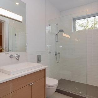 Foto di una stanza da bagno con doccia nordica di medie dimensioni con lavabo a bacinella, ante lisce, ante in legno chiaro, top in quarzo composito, doccia aperta, WC sospeso, piastrelle bianche, piastrelle in ceramica, pareti bianche e pavimento in cemento
