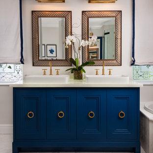 Ejemplo de cuarto de baño principal, tradicional renovado, de tamaño medio, con lavabo sobreencimera, armarios tipo mueble, puertas de armario azules, bañera encastrada, ducha esquinera, baldosas y/o azulejos blancos, baldosas y/o azulejos de piedra y suelo de mármol