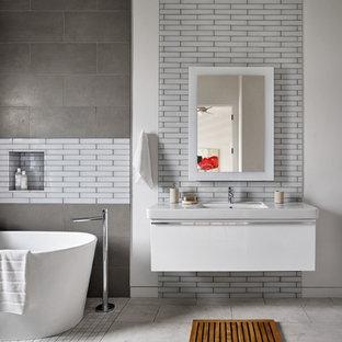 Esempio di un'ampia stanza da bagno padronale design con ante lisce, ante bianche, vasca freestanding, piastrelle di vetro, pareti multicolore, pavimento in gres porcellanato, lavabo sospeso, top in superficie solida e piastrelle bianche
