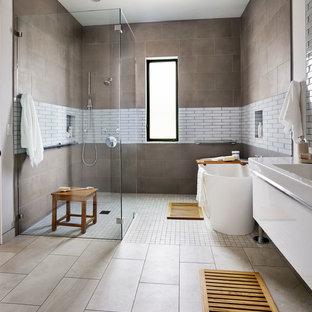 ポートランドの広いビーチスタイルのおしゃれなマスターバスルーム (置き型浴槽、グレーのタイル、グレーの壁、フラットパネル扉のキャビネット、白いキャビネット、人工大理石カウンター、磁器タイル、磁器タイルの床、壁付け型シンク、バリアフリー) の写真