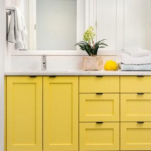 Foto di una grande stanza da bagno con doccia contemporanea con lavabo sottopiano, ante in stile shaker, ante gialle, vasca/doccia, WC sospeso, piastrelle in pietra e pareti bianche