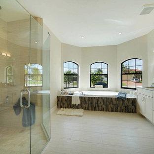 Ispirazione per una stanza da bagno padronale mediterranea di medie dimensioni con ante in stile shaker, ante beige, vasca da incasso, doccia alcova, piastrelle marroni, piastrelle a listelli, pareti beige, pavimento in gres porcellanato, lavabo sottopiano, top in granito, pavimento beige, porta doccia a battente e top beige