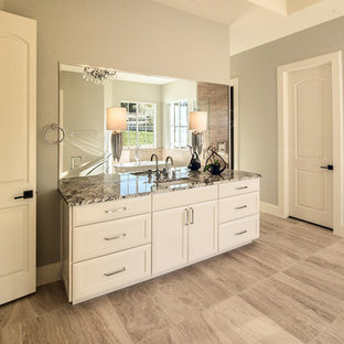 Bathroom - large mediterranean master beige tile and porcelain tile porcelain floor bathroom idea in Austin with white cabinets, white walls, an undermount sink and granite countertops