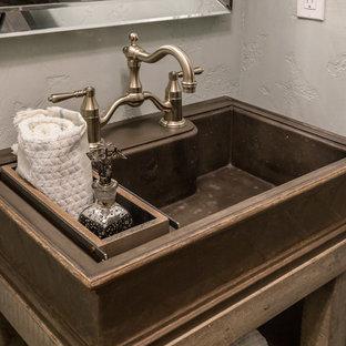 Immagine di una stanza da bagno country con consolle stile comò, ante con finitura invecchiata, WC a due pezzi, pareti verdi, parquet scuro, lavabo a colonna, top in cemento, pavimento marrone e top marrone