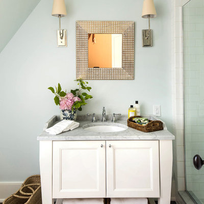 Mid-sized elegant 3/4 white tile and subway tile dark wood floor and brown floor alcove shower photo in Birmingham with white cabinets, recessed-panel cabinets, blue walls, an undermount sink, marble countertops, a hinged shower door and gray countertops