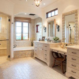 サンディエゴの中くらいの地中海スタイルのおしゃれなマスターバスルーム (家具調キャビネット、ベージュのキャビネット、アルコーブ型浴槽、マルチカラーのタイル、白い壁、バリアフリー、セラミックタイル、トラバーチンの床、アンダーカウンター洗面器、クオーツストーンの洗面台、開き戸のシャワー) の写真