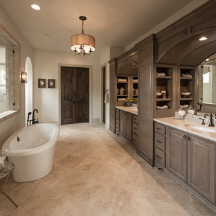 Example of a tuscan master beige floor bathroom design in Austin with medium tone wood cabinets, white walls, raised-panel cabinets, an undermount sink and white countertops