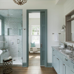 Bathroom - coastal master medium tone wood floor and brown floor bathroom idea in Minneapolis with recessed-panel cabinets, turquoise cabinets, white walls, an undermount sink and a hinged shower door