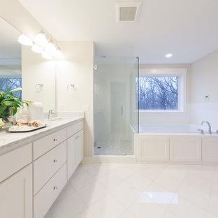 Klassisk inredning av ett stort en-suite badrum, med skåp i shakerstil, vita skåp, ett platsbyggt badkar, en hörndusch, en toalettstol med separat cisternkåpa, vit kakel, tunnelbanekakel, beige väggar, klinkergolv i porslin, ett undermonterad handfat, marmorbänkskiva, vitt golv och dusch med gångjärnsdörr