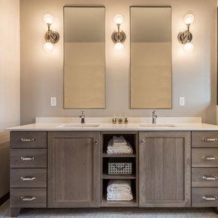 Modelo de cuarto de baño principal, de estilo de casa de campo, con armarios estilo shaker, puertas de armario con efecto envejecido, bañera exenta, ducha empotrada, paredes beige, suelo vinílico, lavabo bajoencimera, encimera de cuarcita, suelo gris y encimeras blancas
