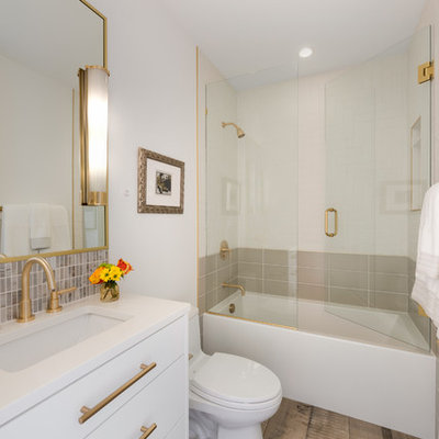 Inspiration for a mid-sized contemporary 3/4 white tile and porcelain tile brown floor and porcelain tile bathroom remodel in Minneapolis with flat-panel cabinets, white cabinets, white walls, an undermount sink, a hinged shower door, white countertops, a one-piece toilet and quartz countertops