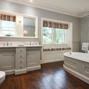 Classic ensuite bathroom in Other with shaker cabinets, grey cabinets, a built-in bath, a corner shower, white tiles, grey walls, a submerged sink, brown floors and a hinged door.