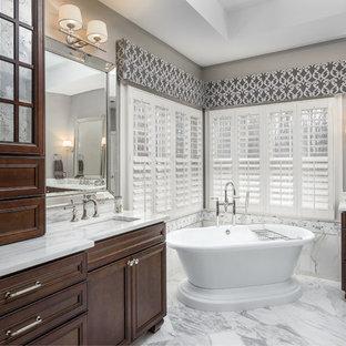 Diseño de cuarto de baño principal, clásico renovado, grande, con armarios tipo mueble, puertas de armario de madera en tonos medios, bañera exenta, baldosas y/o azulejos blancos, baldosas y/o azulejos de mármol, paredes grises, suelo de mármol, lavabo bajoencimera, encimera de mármol, suelo blanco y encimeras turquesas