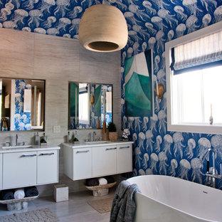 Maritimes Badezimmer En Suite mit flächenbündigen Schrankfronten, weißen Schränken, freistehender Badewanne, blauer Wandfarbe, Wandwaschbecken und weißer Waschtischplatte in New York