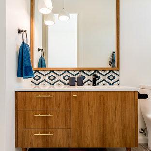 他の地域の中サイズのミッドセンチュリースタイルのおしゃれなバスルーム (浴槽なし) (フラットパネル扉のキャビネット、中間色木目調キャビネット、アルコーブ型浴槽、シャワー付き浴槽、一体型トイレ、マルチカラーのタイル、セラミックタイル、白い壁、セラミックタイルの床、アンダーカウンター洗面器、珪岩の洗面台、グレーの床、シャワーカーテン、白い洗面カウンター) の写真