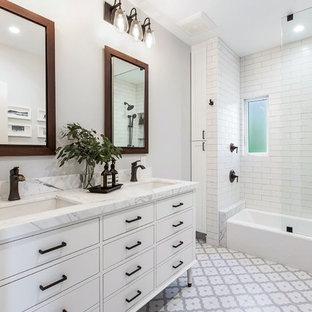 Foto på ett mellanstort vintage vit en-suite badrum, med släta luckor, vita skåp, ett badkar i en alkov, en dusch/badkar-kombination, vit kakel, keramikplattor, grå väggar, klinkergolv i porslin, ett undermonterad handfat, flerfärgat golv och med dusch som är öppen