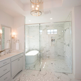 Large transitional master gray tile and marble tile marble floor and gray floor bathroom photo in Milwaukee with furniture-like cabinets, gray cabinets, a two-piece toilet, white walls, an undermount sink, quartz countertops, a hinged shower door and white countertops