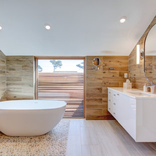 Example of a trendy master wood-look tile brown floor and vaulted ceiling freestanding bathtub design in Other with flat-panel cabinets, white cabinets, brown walls, an undermount sink and white countertops