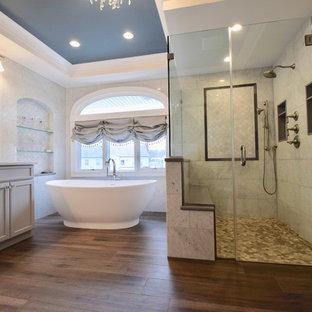 Свежая идея для дизайна: большая главная ванная комната в классическом стиле с фасадами с утопленной филенкой, серыми фасадами, отдельно стоящей ванной, душем без бортиков, унитазом-моноблоком, белой плиткой, серыми стенами, полом из керамогранита, врезной раковиной, столешницей из искусственного кварца, коричневым полом, душем с распашными дверями, белой столешницей, сиденьем для душа, тумбой под две раковины, напольной тумбой, многоуровневым потолком и кирпичными стенами - отличное фото интерьера