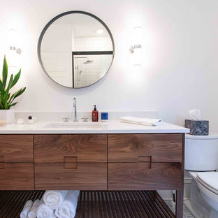 Mid-sized transitional 3/4 white tile porcelain tile, multicolored floor and single-sink bathroom photo in Minneapolis with flat-panel cabinets, medium tone wood cabinets, a one-piece toilet, gray walls, an undermount sink, quartz countertops, white countertops and a freestanding vanity