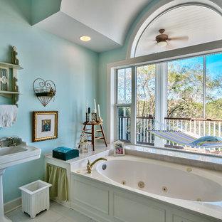 Modelo de cuarto de baño ecléctico con lavabo con pedestal, bañera encastrada y paredes azules