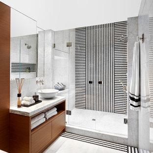 На фото: ванная комната среднего размера в современном стиле с плоскими фасадами, фасадами цвета дерева среднего тона, душем в нише, черной плиткой, черно-белой плиткой, белой плиткой, плиткой мозаикой, душевой кабиной, настольной раковиной, разноцветным полом, душем с распашными дверями, серыми стенами и мраморной столешницей с