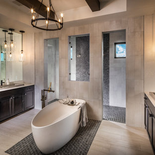 オースティンの巨大なコンテンポラリースタイルのおしゃれなマスターバスルーム (濃色木目調キャビネット、置き型浴槽、ダブルシャワー、磁器タイルの床、オーバーカウンターシンク、シェーカースタイル扉のキャビネット、ベージュのタイル、ベージュの壁、ベージュの床、ベージュのカウンター) の写真