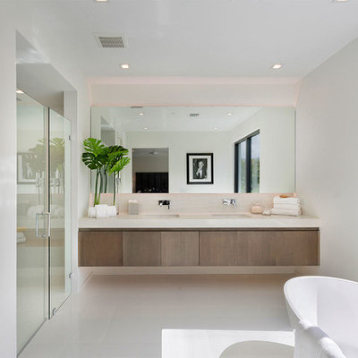Example of a trendy master white floor bathroom design in Miami with flat-panel cabinets, medium tone wood cabinets, white walls, an undermount sink, a hinged shower door and white countertops